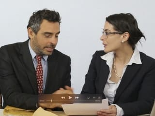 A businessman and busines woman sitting and discussing some paperwork.