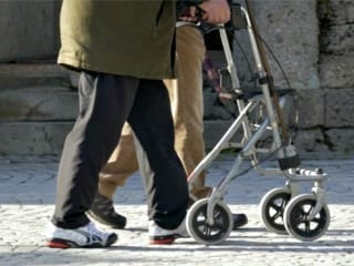 An elderly man pushing a wheeled walking aid.