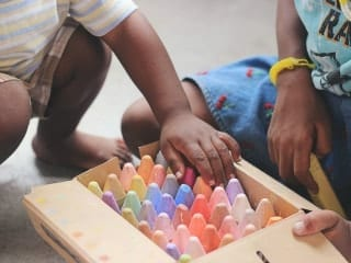 A box of extra large coloured chalks with a child's hands seen reaching in.